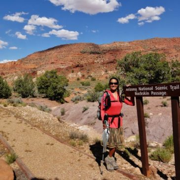 Woman with backpack stands next to sign that says Arizona National Scenic Trail, Buckskin Passage