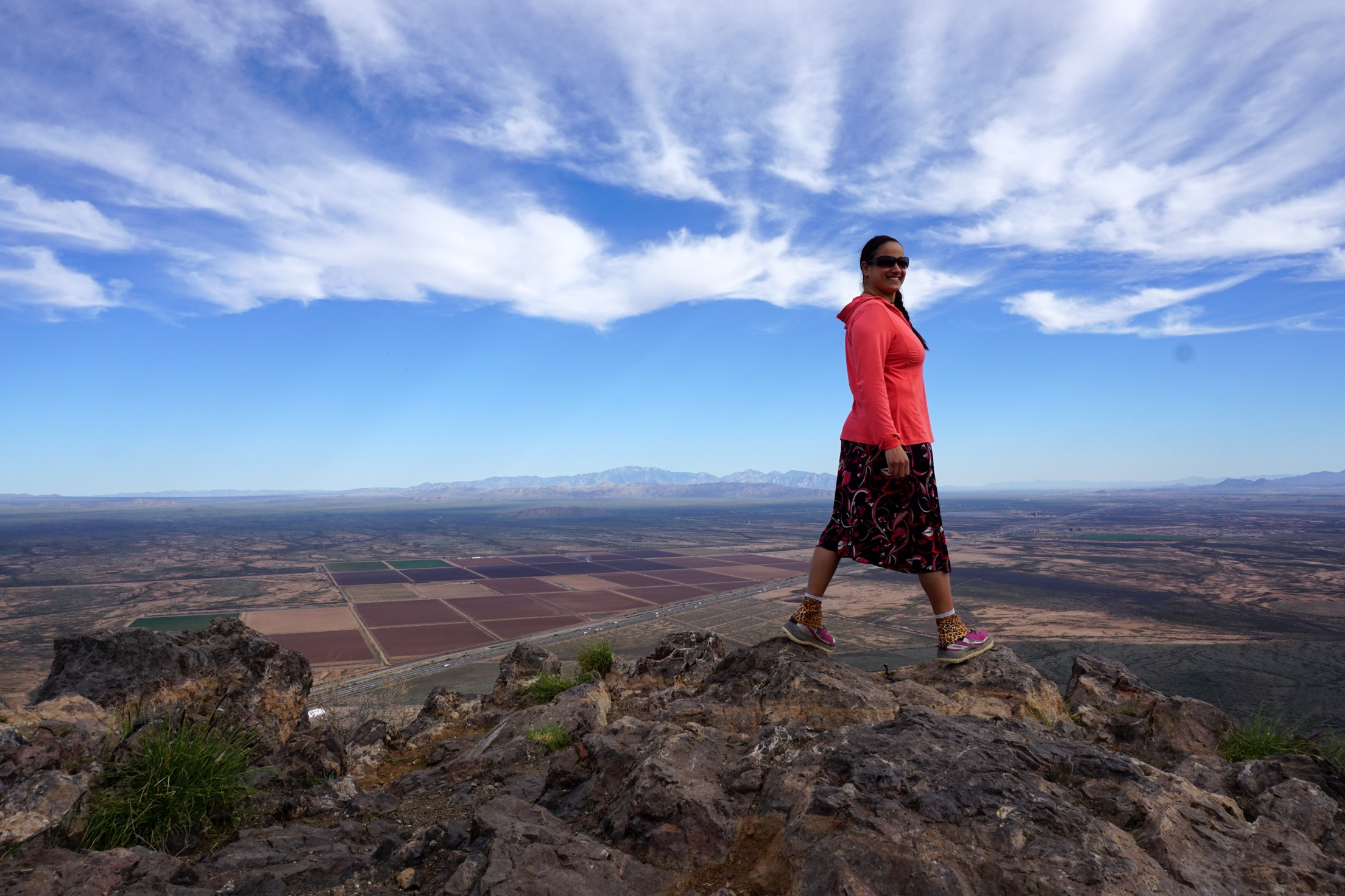 Sirena Rana Dufault stands in a pink top and floral skirt  atop Picacho Peak